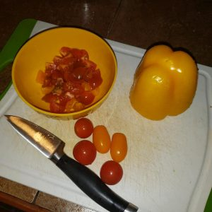 chopped tomatoes and pepper on cutting board